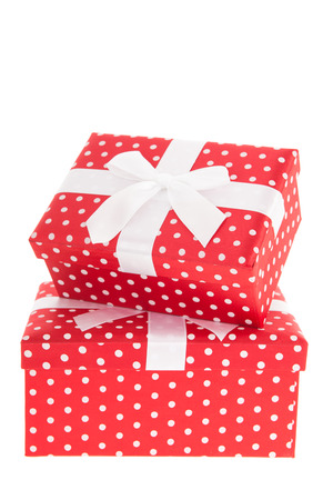 Red dotted presents with ribbon and satin bow isolated over white background photo