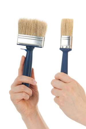refurbish: Hands with paint brushes for refurbish the house