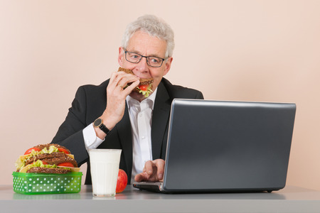 Senior man eating with lunch box and working with laptop at the office photo