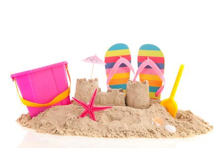 castillos: Castillo de arena andd juguetes en la playa aislada sobre fondo blanco