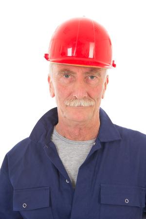 casco rojo: Trabajador senior en ropa de trabajo azul y casco de color rojo aisladas sobre fondo blanco Foto de archivo