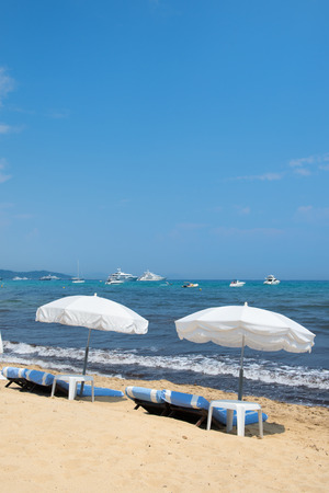 mundane: Beach with parasols, beds and luxury yachts Stock Photo