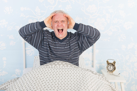neighbours: Man at night having problems with noise from the neighbours above Stock Photo