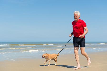 hombre rojo: Corredor mayor con el perro en la playa Foto de archivo
