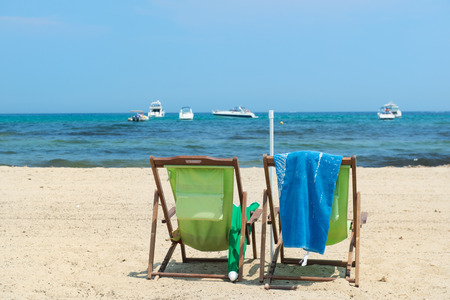 mundane: Luxury beach with parasols,green chairs and luxury yachts