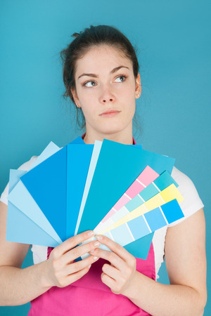 refurbish: Woman with color samples against blue wall