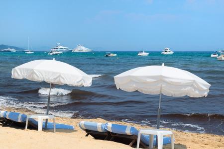 mundane: Beach with parasols, beds and luxury yachts Stock Photo