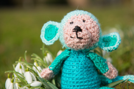 selfmade: crocheted selfmade monkey toy sitting in flowers outdoor