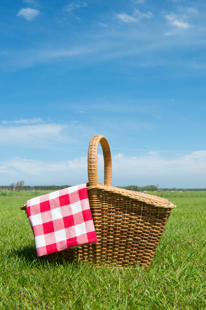 basket: Picnic basket in grass outdoor Stock Photo
