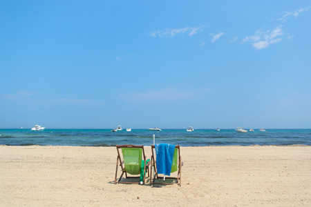 mundane: Beach with empty chairs in green and blue Stock Photo