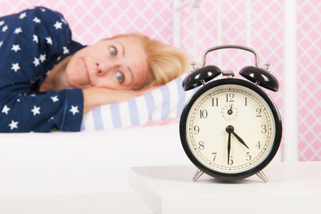 Blond woman of mature age with insomnia and big alarm clock - focus point on clock Foto de archivo