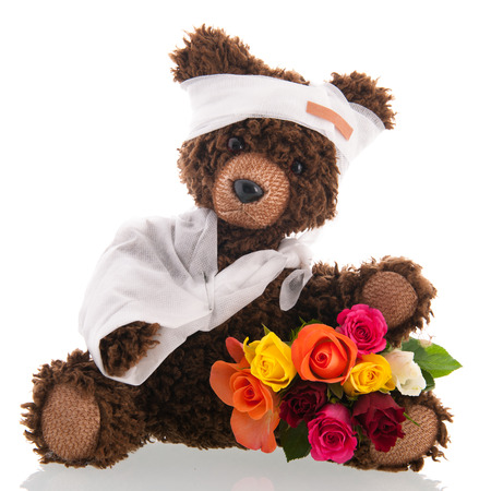 Stuffed hand made poorly bear with plaster and flowers for Get well soon isolated over white background
