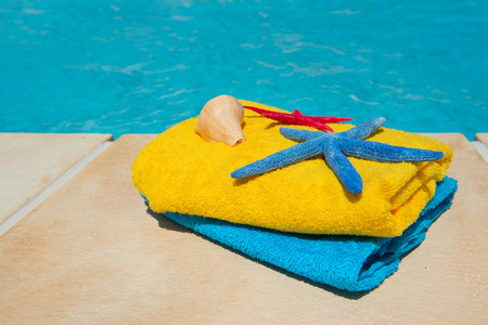 accomodation: Towels in blue and yellow at the swimming pool Stock Photo