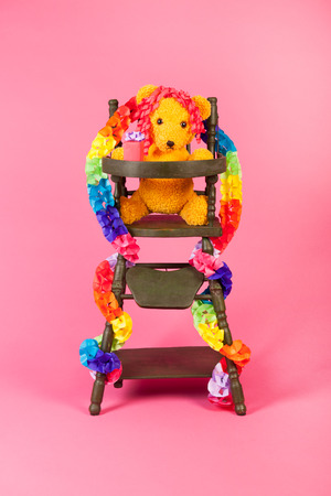 craftwork: Stuffed birthday bear with present in child chair on pink background