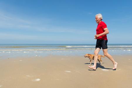 fila de personas: Corredor mayor con el perro en la playa Foto de archivo