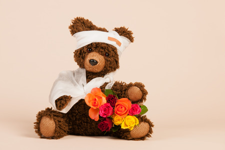animal hand: Stuffed hand made bear with pain plaster and flowers isolated over white background
