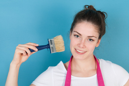 refurbish: Woman with apron and paint brush against blue wall