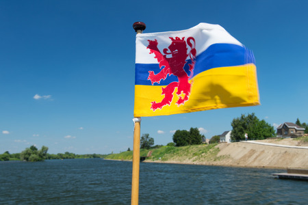 meuse: Flag Dutch province Limburg on ferry boat at the Meuse