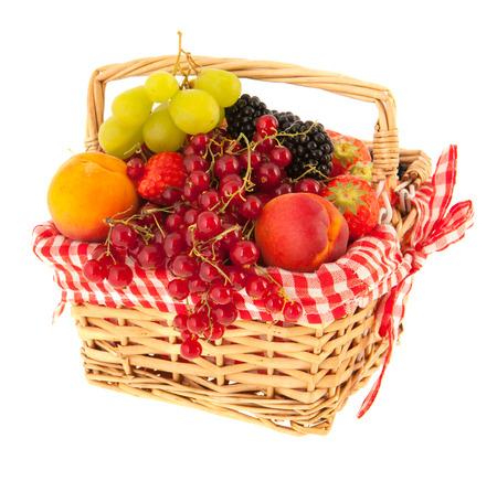 Basket full with fresh summer fruit isolated over white background photo