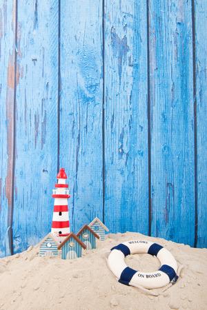fondo vintage azul: Playa con el faro y la boya de vida delante de fondo azul de la vendimia