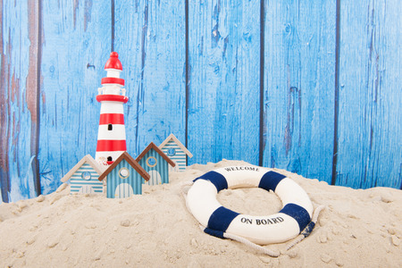 beach buoy: Beach with lighthouse and life buoy in front of vintage blue background