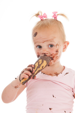 ice cram: Portrait toddler girl eating chocolate ice cream isolated over white background