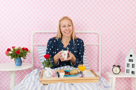 mothersday: Woman of mature age eating breakfast on bed Stock Photo