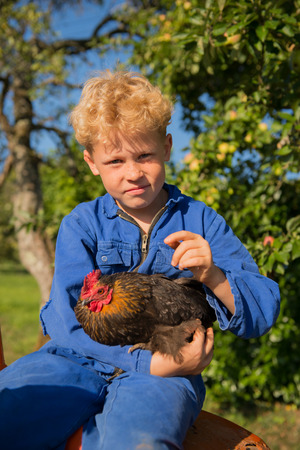 coverall: Farm boy with chicken riding on orange tractor
