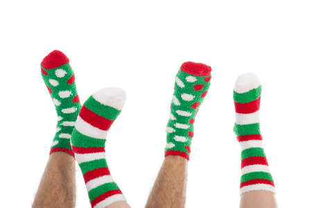 Many feet in Christmas socks isolated over white background Stock Photo