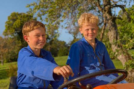 coverall: Farm boys riding on orange tractor
