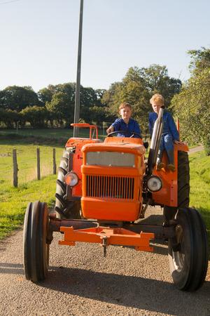 farm boys: Farm boys riding on orange tractor