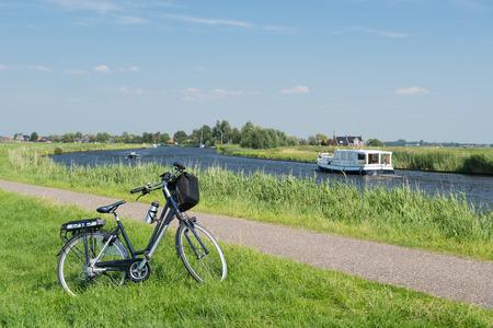 Typisch Nederlands landschap met rivierwater en fiets