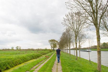 Man lopen van de hond in een typisch Nederlands landschap Stockfoto - 48478430
