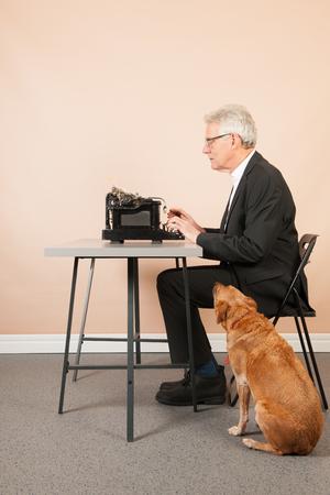 Senior man writing with Antique black typewriter and dog