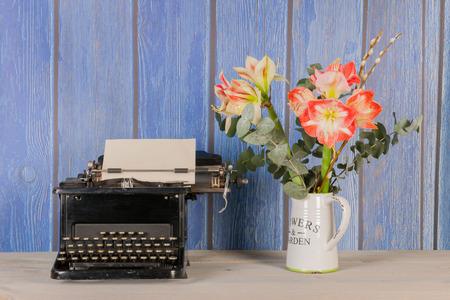 Antique black typewriter in interior with vase flowers