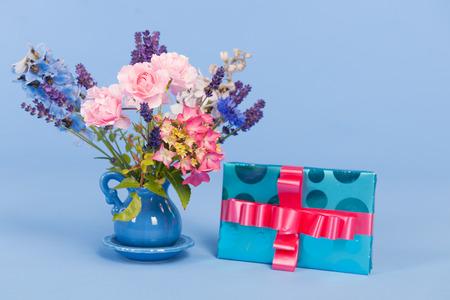 flor morada: ramo de flores coloridas en florero en el fondo azul