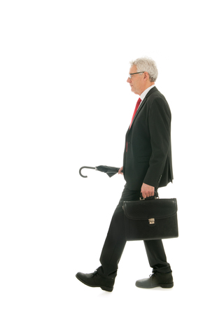 formally: Formally dressed Senior business man with umbrella and case