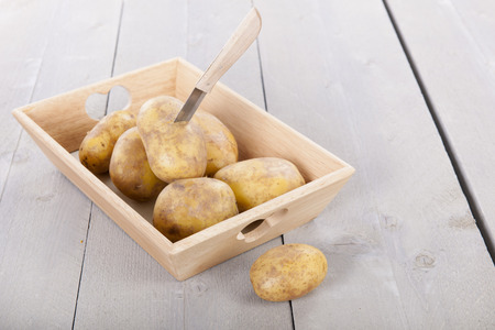 them: Basket raw potatoes and knife to peel them