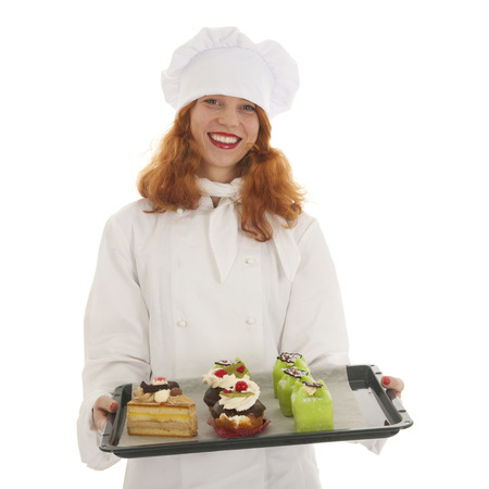 christmas baker's: Female baker chef with red hair proud with baked Christmas pastries isolated over white background Stock Photo
