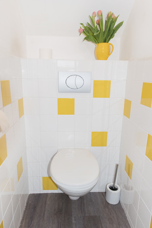 health care facilities: Modern toilet with yellow tiles Stock Photo