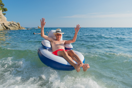 humor: Senior man on vacation floating on chair in the sea