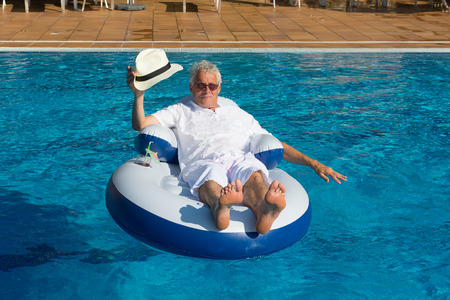 wealthy man relaxing in own swimming pool Stock Photo