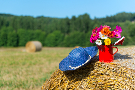 hayroll: Bouquet garden flowers and summer hat on hay roll in summertime
