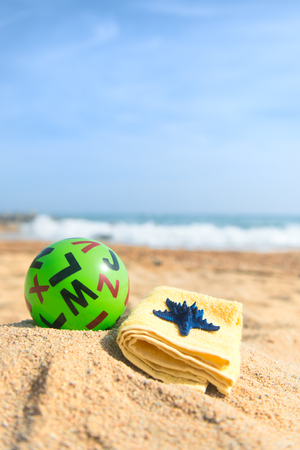 Green toy ball with letters at the beach Stock Photo