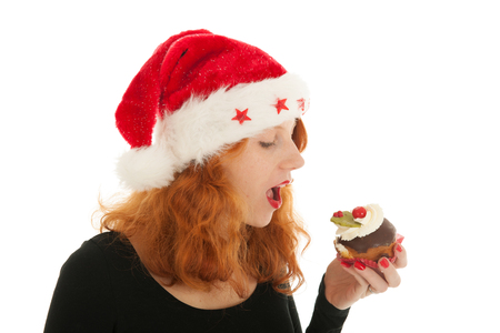 female christmas: Young red haired Christmas girl eating cake with cream