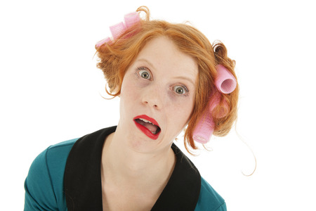 gaping: Funny young woman with curlers and lipstick isolated in studio