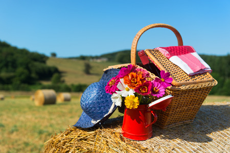 hayroll: Bouquet garden flowers picnic basket and summer hat on hay roll in summertime