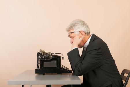 correspond: Senior man writing with Antique black typewriter
