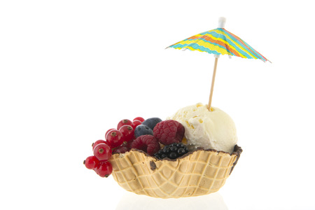 Cup from cookie with vanilla ice and fresh fruit with parasol isolated over white background