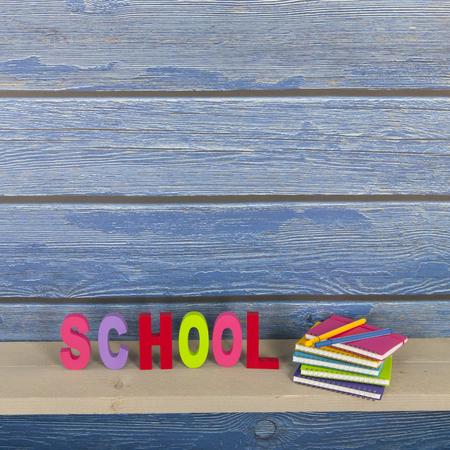 School in colorful letters and notebooks with vintage blue wooden wall